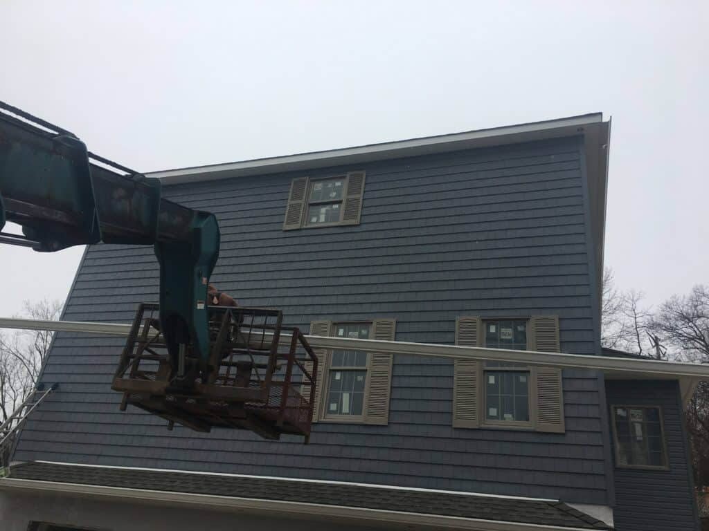 installing new gutters on a high roofline with a lift
